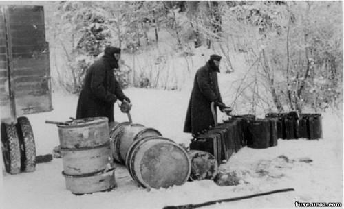 Солдаты вермахта с поднятыми на морозе воротниками вручную заправляют канистры из 200 литровых бочек.